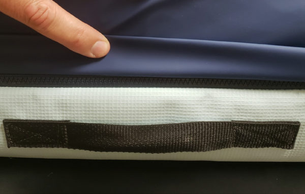 an image of a finger, pulling up the fabric cover, over a zipper on a mattress. also show, a black handle on the side of a mattress